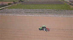 Aerial view of agricultural tractor sowing seeds on plowed field - stock footage