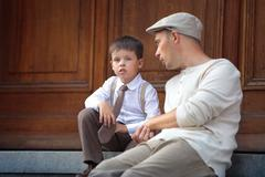 Happy father and son talking outdoors in city Stock Photos