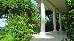 Porch in tropical garden with white columns and ocean Stock Footage