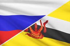 flag of russia and brunei blowing in the wind. part of a series. - stock illustration