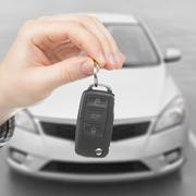 male holding car keys with remote control system - stock photo
