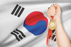 Stock Photo of sportsman holding gold medal with flag on background - south korea