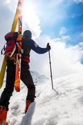 ski mountaineer walking up along a steep snowy ridge with the skis in the bac - stock photo