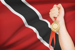 sportsman holding gold medal with flag on background - republic of trinidad a - stock photo