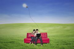Couple using laptop on red sofa with lamp outdoor Stock Photos