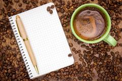 Stock Photo of notebook pen and cup of coffee