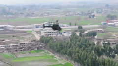 War in Afghanistan - OH-58D Kiowa Warriors - Helicopter over residential area Stock Footage