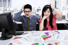 Stressed businessteam analyzing business chart Stock Photos