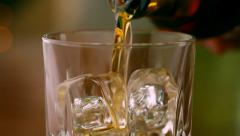 Pouring a scotch whiskey into glass with ice Stock Footage