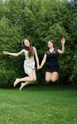 two young cheerful women jumping - stock photo