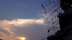 Storm damaged scaffolding surrounds a Buddha at dusk - BM1 Stock Footage
