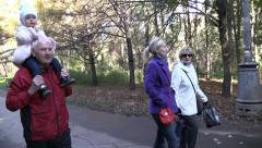 Stock Video Footage of Happy Family on walk in autumn park. Steady Fly Cam.