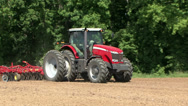 Stock Video Footage of Red Commercial Tractor Pulling Plow in Dirt Field Sunny Day