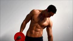 Young handsome male bodybuilder training obliques and abs muscles with dumbbells - stock footage