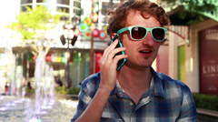 Young man talking on a cell phone in a busy town square Stock Footage