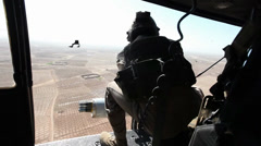 War in Afghanistan - Helicopter Door Gunner Fires on Enemy Targets rear view Stock Footage