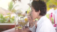 Woman drinks margarita on the beach bar Stock Footage