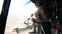 War in Afghanistan  - Helicopter door gunner scouting Stock Footage