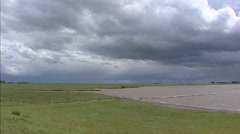 DOLLARD BAY  reclaimed land at Dutch Coast, storm clouds and showers + pan. Stock Footage