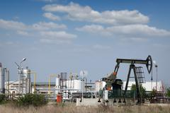 oilfield with oil pump jack and refinery - stock photo