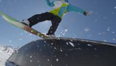 SLOW MOTION: Snowboarder rides a rainbow box Stock Footage