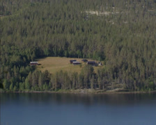Settlement at lakeside, Lake Atna, Norway + pan pine forest wilderness and lake - stock footage