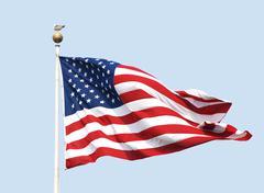 Yhdysvaltain lippu lentää aurinkoisena päivänä vastaan selkeä sininen taivas. Kuvituskuvat