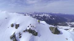 Stock Video Footage of AERIAL: Extreme freeride skier skiing on top of the mountain