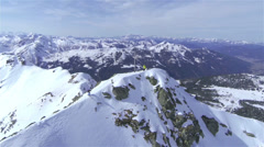 AERIAL: Backcountry skier riding down the big mountain - stock footage