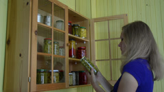 Lady take glass jar with canned olive and mushrooms from cabinet Stock Footage