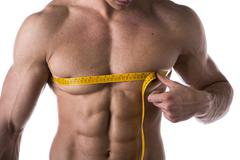 muscular shirtless young man measuring chest and pecs with tape measure - stock photo