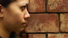 Pimple faced lady peeps through brick wall Stock Footage
