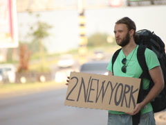 Hitchhiking young adult man displaying 2 new york written sign Stock Footage