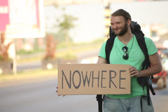 Hitchhiking young adult man displaying nowhere written sign board Stock Footage