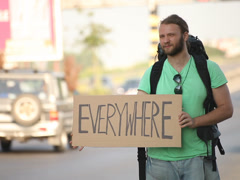 Hitchhiking young adult man displaying everywhere written sign board Stock Footage