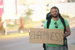 Hitchhiking young adult man displaying 2 happiness written sign board Stock Footage