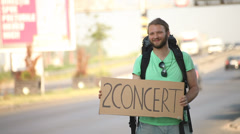 Hitchhiking young adult man displaying 2 concert written sign board Stock Footage