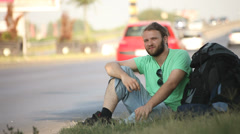 hitchhiking young adult man hitchhiker waiting by highway - stock footage