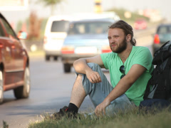 Hitchhiking young adult man hitchhiker waiting by highway Stock Footage
