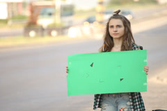 Hitchhiking young adult woman hitchhiker holding empty green board Stock Footage