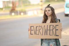 Hitchhiking young adult woman hitchhiker holding everywhere written board Stock Footage
