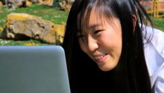 Dolly shot of closeup of happy chinese american girl working with computer in - stock footage