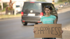 Hitchhiking young adult woman hitchhiker holding 2 happiness written board Stock Footage