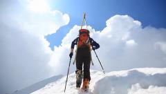 Ski mountaineer walking up along a steep snowy ridge Stock Footage