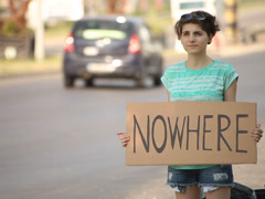 Hitchhiking young adult woman hitchhiker holding nowhere written board Stock Footage