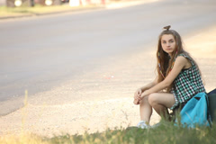 Hitchhiking young adult woman hitchhiker pointing thumb up Stock Footage