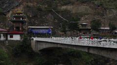 Bicyclists riding over bridge in Bhutan Stock Footage