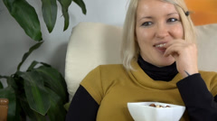 Mother to be eats snack and laughs out loud while watching television - stock footage