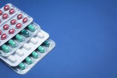 Some pills aligned isolated on blue background Stock Photos