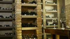 Glasses of wine in cellar filled with bottles Stock Footage
